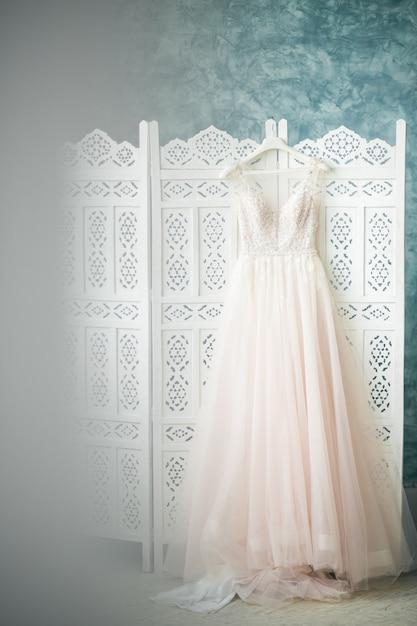 Vestido da noiva pendurada no quarto Foto gratuita