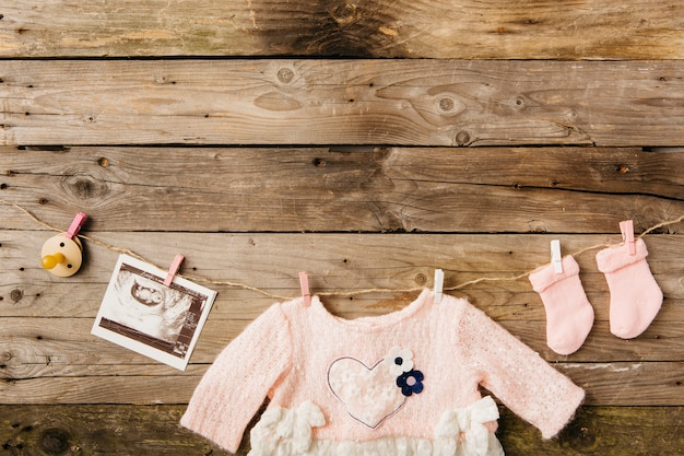 Vestido de bebê; meias; imagens de chupeta e sonografia pendurado no varal com prendedores de roupa contra a parede de madeira Foto gratuita