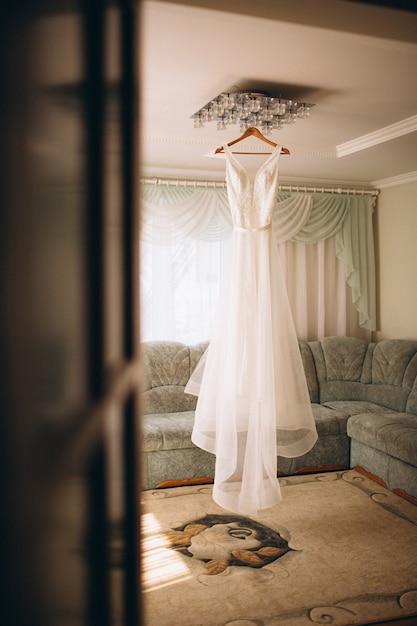 Vestido de casamento da noiva pendurado no quarto Foto gratuita