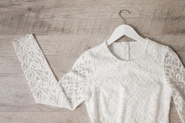 Vestido de noiva branco do laço no cabide contra o plano de fundo texturizado de madeira Foto gratuita