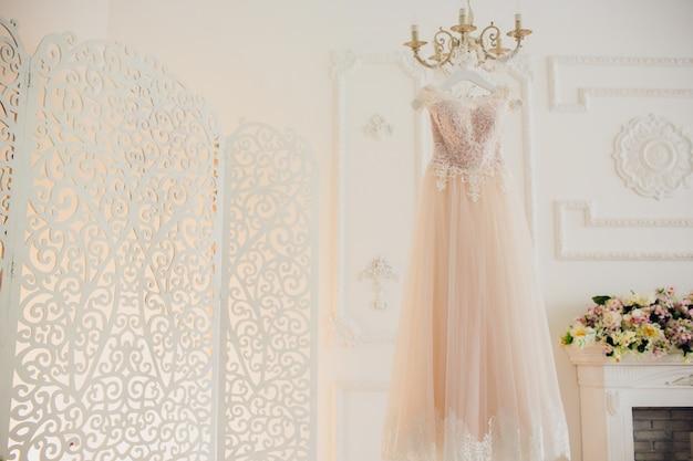 Vestido de noiva pendurado no brilho no quarto de hotel. Foto Premium