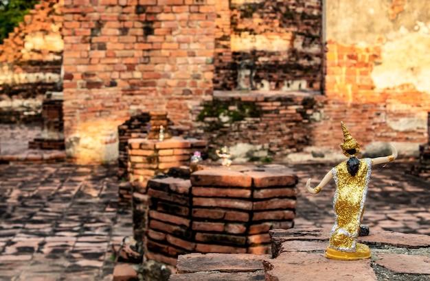 Vestido tailandês das bonecas nos tijolos do assoalho em um templo abandonado. Foto Premium