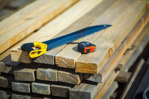 Vi com uma fita métrica de construção em tábuas de madeira. serra. fita de construção. tábuas de madeira Foto Premium