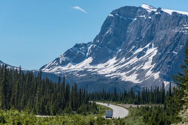 Viagem de carro com uma excelente vista da grande montanha e céu azul em alberta, canadá Foto Premium