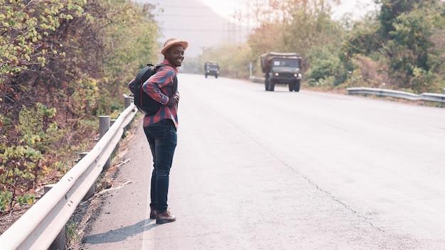 Viagem de homem africano carregando mochila andando na estrada da estrada. conceito de dia do turismo Foto Premium