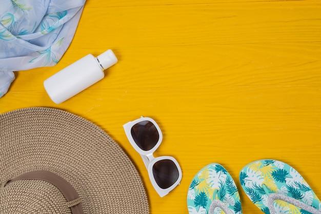 Viagem marítima, chapéu, óculos escuros, óculos, sandálias coloc no chão de madeira amarelo. Foto gratuita