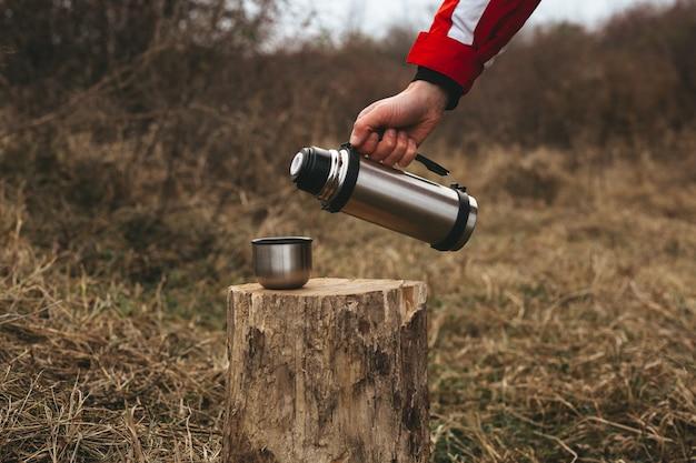 Viagem temática. o homem derrama uma bebida quente na caneca térmica em um tronco de madeira Foto Premium