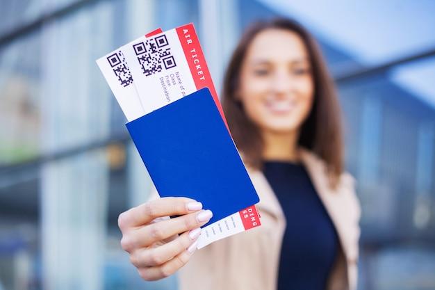 Viagens, mulher segurando duas passagens aéreas no exterior passaporte perto do aeroporto Foto Premium