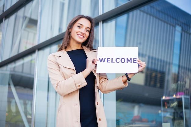 Viagens, negócios de mulheres com o cartaz com mensagem de boas-vindas Foto Premium