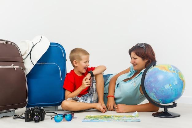 Viajando com crianças. mãe feliz com seu filho roupas de embalagem para as suas férias Foto Premium