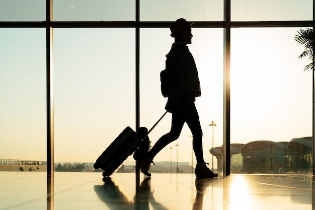 Viajante a pé com mala, passageiro para passeio no terminal do aeroporto para viagens aéreas Foto Premium