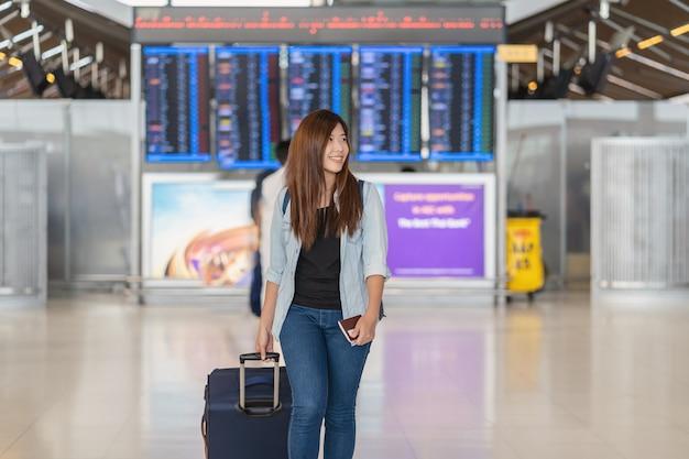 Viajante asiático com bagagem com passaporte andando sobre a placa de voo para check-in Foto Premium