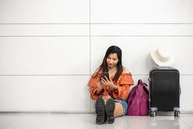 Viajante asiático feminino à espera de voo e usando telefone inteligente fora do salão no aeroporto Foto Premium