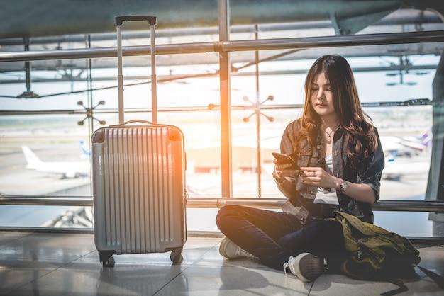 Viajante asiático feminino usando telefone inteligente para verificar o horário de voo no aeroporto Foto Premium