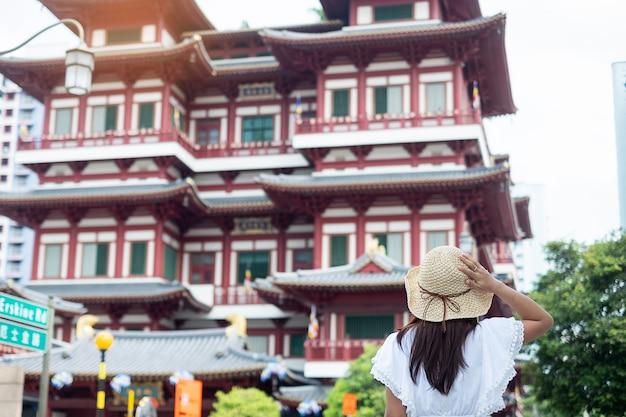 Viajante asiático olhando para o templo de relíquia do dente de buda em chinatown singapura Foto Premium