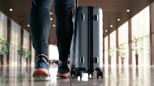 Viajante com mala andando com o transporte de bagagem e passageiro para passeio no terminal do aeroporto para viagens aéreas Foto Premium