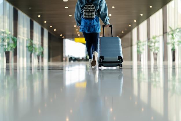 Viajante com mala andando com transporte de bagagem no terminal do aeroporto Foto Premium
