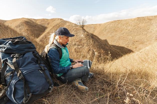 Viajante com mochila e laptop ao ar livre Foto gratuita