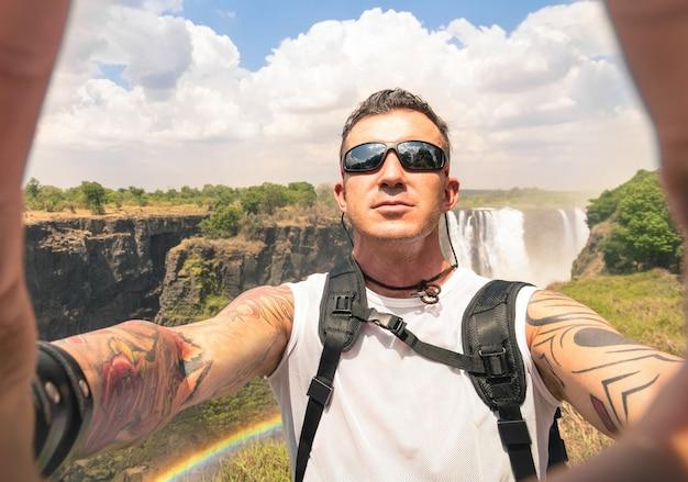 Viajante com tatuagens tomando selfie em victoria falls Foto Premium