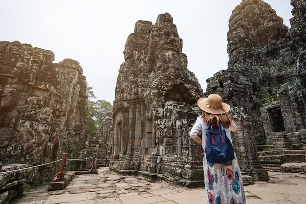 Viajante da jovem mulher que visita no templo de bayon no complexo de angkor wat Foto Premium