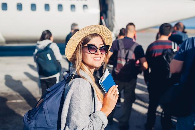 Viajante da mulher que embarca no avião que guarda o passaporte. feliz passageiro com mochila na fila pronta para o voo Foto Premium