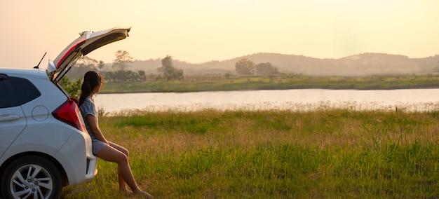 Viajante da mulher que senta-se no carro relaxe da semana do trabalho na noite no meio da natureza. Foto Premium