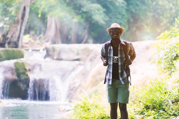Viajante de homem africano com pé de mochila e relaxante liberdade na cachoeira Foto Premium