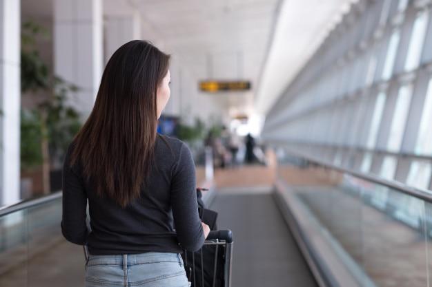 Viajante de jovem caminhando na escada rolante com carrinho de bagagem no aeroporto Foto Premium