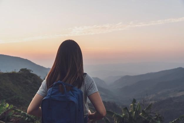 Viajante de jovem mulher olhando o pôr do sol sobre a montanha Foto Premium