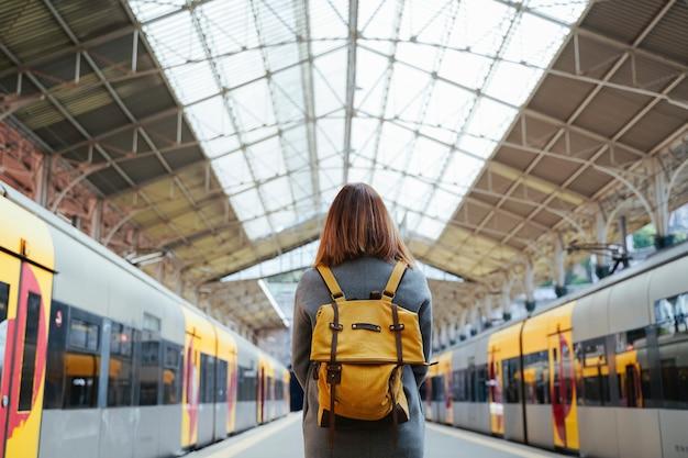 Viajante de linda mulher portuguesa esperando no estação de trem. conceito de viagens e férias. estilo de vida urbano. Foto Premium
