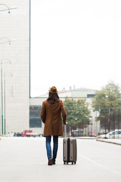Viajante de longa distância com casaco e bagagem Foto gratuita