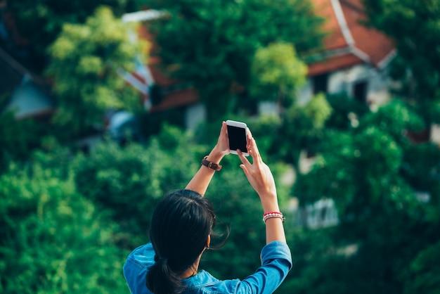 Viajante de mulher asiática na vista traseira usado telefone inteligente lê Foto Premium
