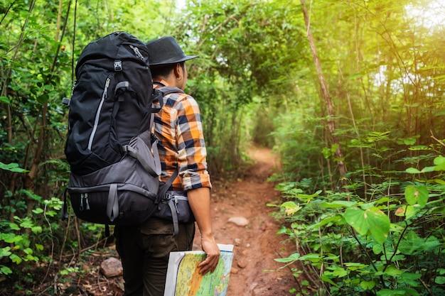 Viajante do homem com mochila e mapa na floresta Foto Premium