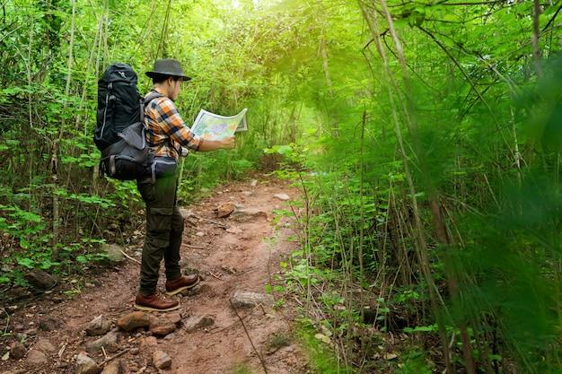 Viajante do homem com mochila e mapa pesquisando direções na floresta Foto Premium