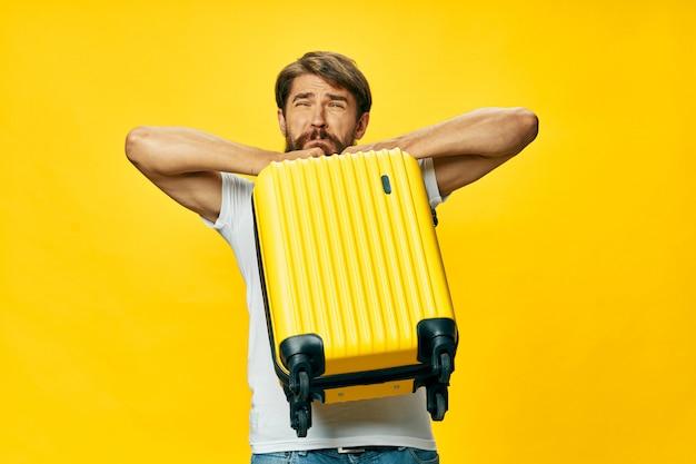 Viajante do sexo masculino com uma mala nas mãos posando, férias Foto Premium