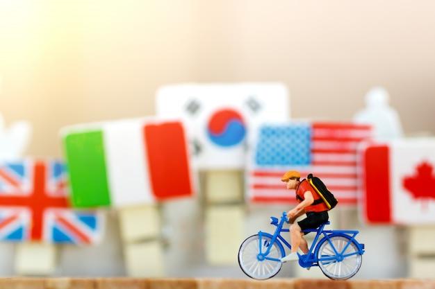 Viajante em miniatura com bicicleta Foto Premium