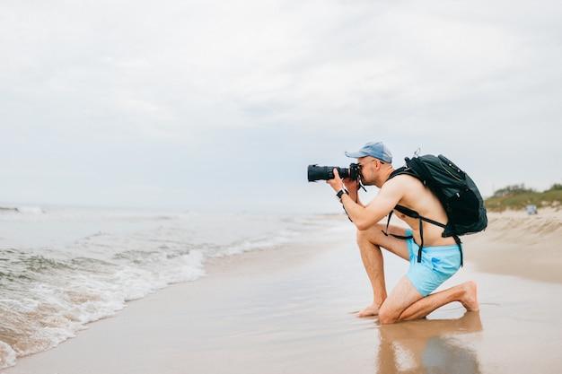Viajante em topless com câmera fotográfica tirando foto do mar. Foto Premium