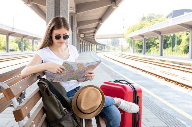 Viajante esperando o trem e olhando o mapa Foto gratuita