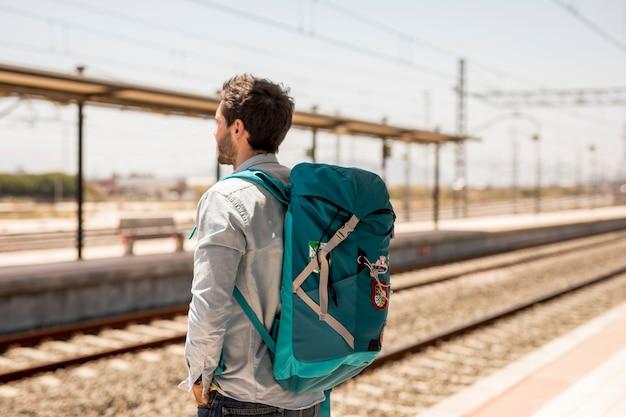 Viajante esperando por trem na plataforma da estação Foto gratuita