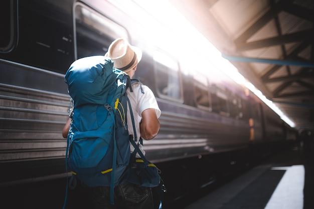 Viajante estão mochilando e andando sozinho na estação de trem. Foto Premium