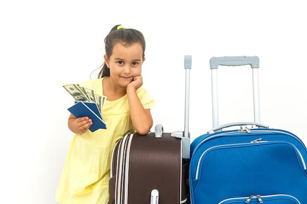 Viajante feliz da criança que mostra o passaporte com a bagagem isolada no conceito branco, do curso e das férias Foto Premium
