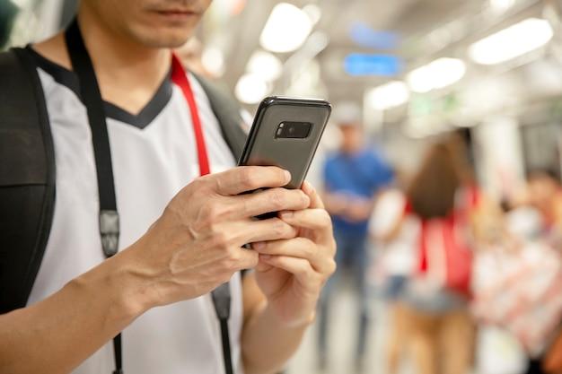 Viajante homem usando smartphone em uma estação de trem Foto Premium