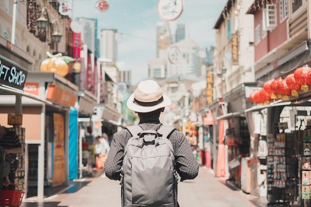 Viajante individual que anda no mercado de rua de chinatown em singapura. Foto Premium