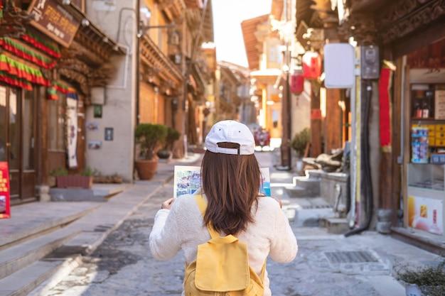 Viajante jovem andando na cidade velha, shangri-la e olhando o mapa, conceito de viagens Foto Premium