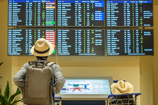Viajante jovem com chapéu, verificando o tempo de voo Foto Premium