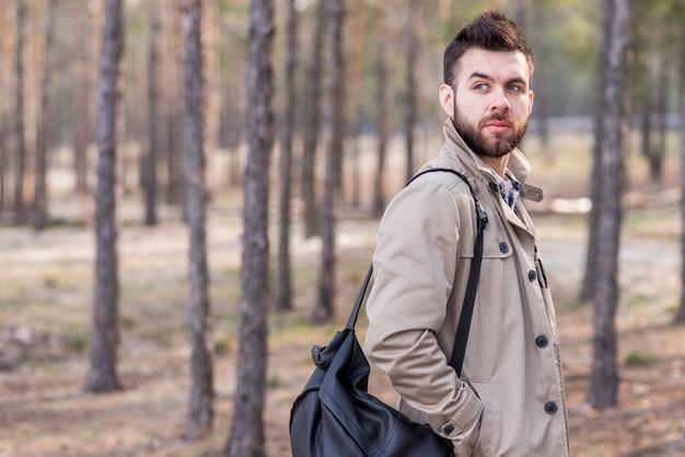 Viajante masculino bonito com a mochila no ombro, olhando para longe Foto gratuita