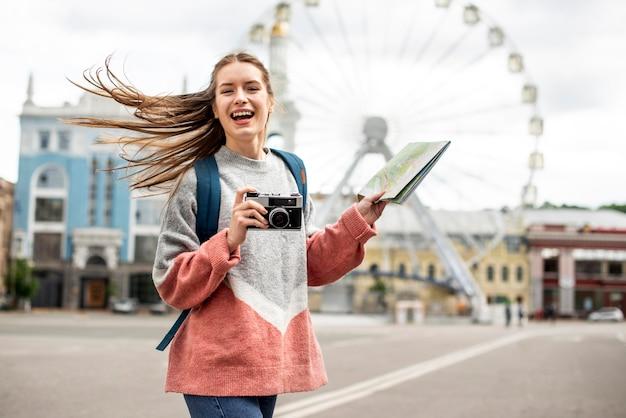 Viajante na cidade e roda gigante atrás Foto gratuita