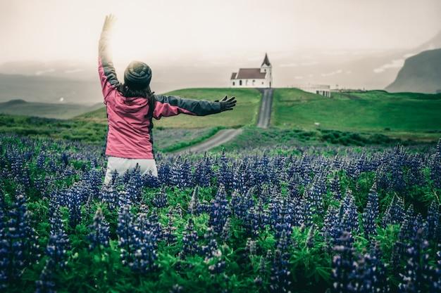 Viajante na islândia. igreja e tremoço flores. Foto Premium