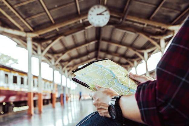 Viajante olhando o mapa enquanto aguarda o trem na estação de trem. conceito de viagens. Foto Premium