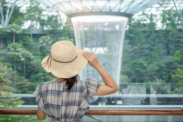 Viajante olhando para o vórtice de chuva linda no aeroporto de jewel changi Foto Premium
